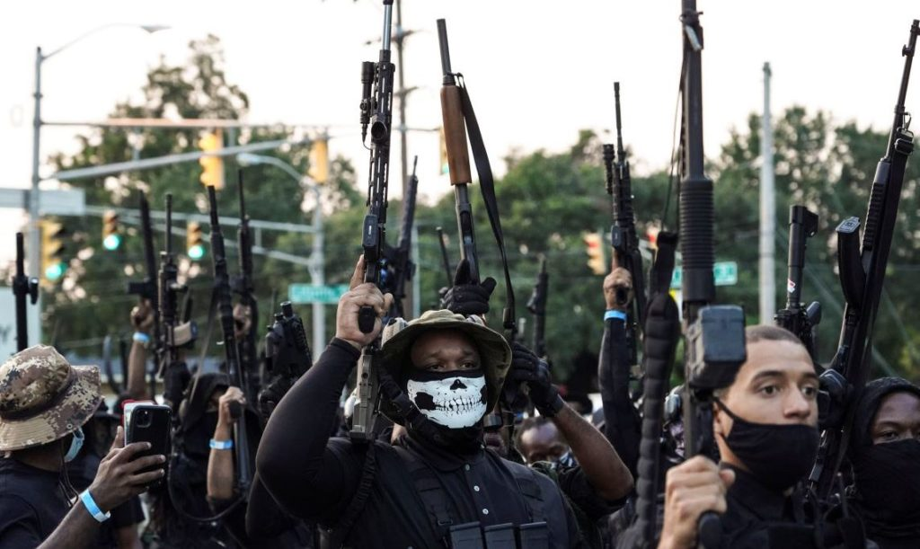 Members of a Black militia group called the NFAC raise their guns while holding an armed rally in Lafayette, Louisiana, U.S. October 3, 2020. REUTERS/Go Nakamura - RC2CBJ9BKSP3