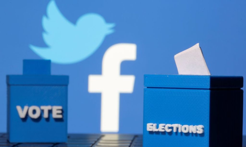 3D printed ballot boxes are seen in front of displayed Facebook and Twitter logos in this illustration taken November 4, 2020. REUTERS/Dado Ruvic/Illustration - RC2KWJ9QT5M8