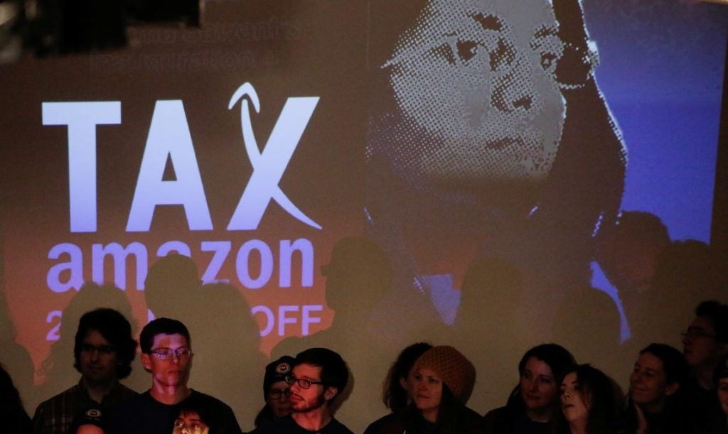"""Members of the United Auto Workers Local 2121 listen while on stage as Socialist Seattle City Council member Kshama Sawant restarts the """"Tax Amazon"""" campaign she led in 2019 with a rally at Washington Hall in Seattle, Washington, U.S. January 13, 2020.  REUTERS/David Ryder - RC2HFE9AFPMJ"""