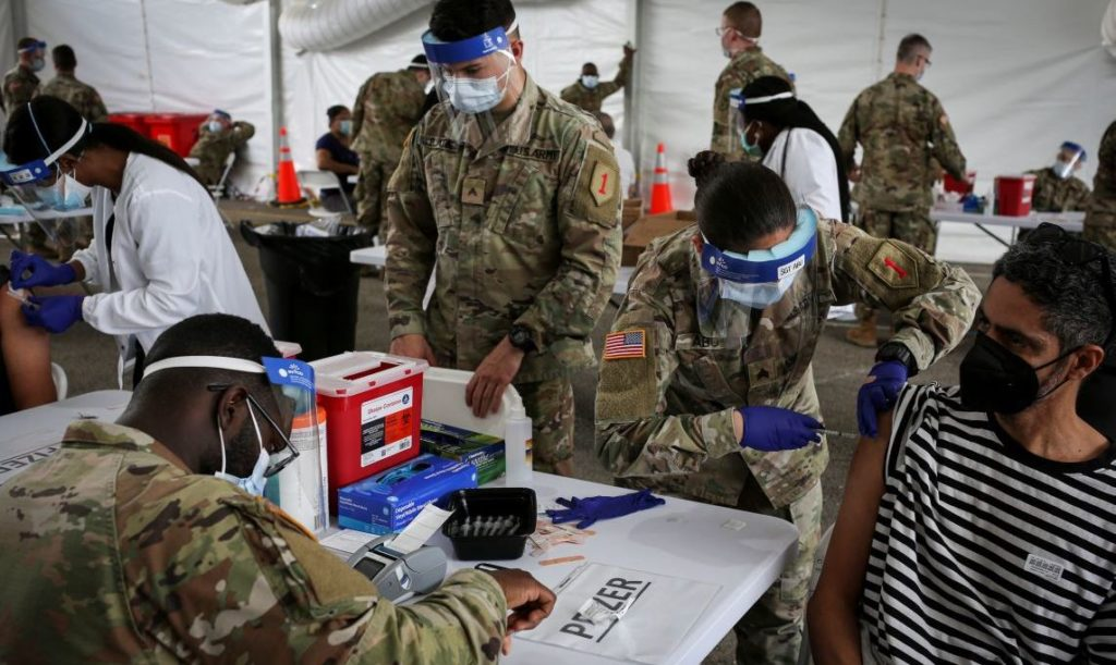 A U.S. Army soldier from the 2nd Armored Brigade Combat Team, 1st Infantry Division, inoculates a man with a Pfizer coronavirus disease (COVID-19) vaccine in a mass vaccination site supported by the federal government at the Miami Dade College North Campus in Miami, Florida, U.S., March 10, 2021. REUTERS/Marco Bello - RC2K8M9HBS7R