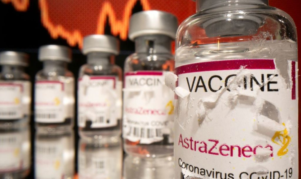 """Vials labelled with broken sticker """"AstraZeneca COVID-19 Coronavirus Vaccine"""" are seen in front of a displayed stock graph in this illustration taken March 15, 2021. REUTERS/Dado Ruvic/Illustration - RC2XBM9BKIWH"""