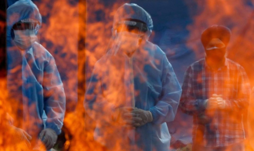 Relatives stand next to the burning pyre of a man who died from the coronavirus disease (COVID-19) during his cremation at a crematorium ground in Srinagar May 25, 2021. REUTERS/Danish Ismail     TPX IMAGES OF THE DAY - RC20NN959HM5