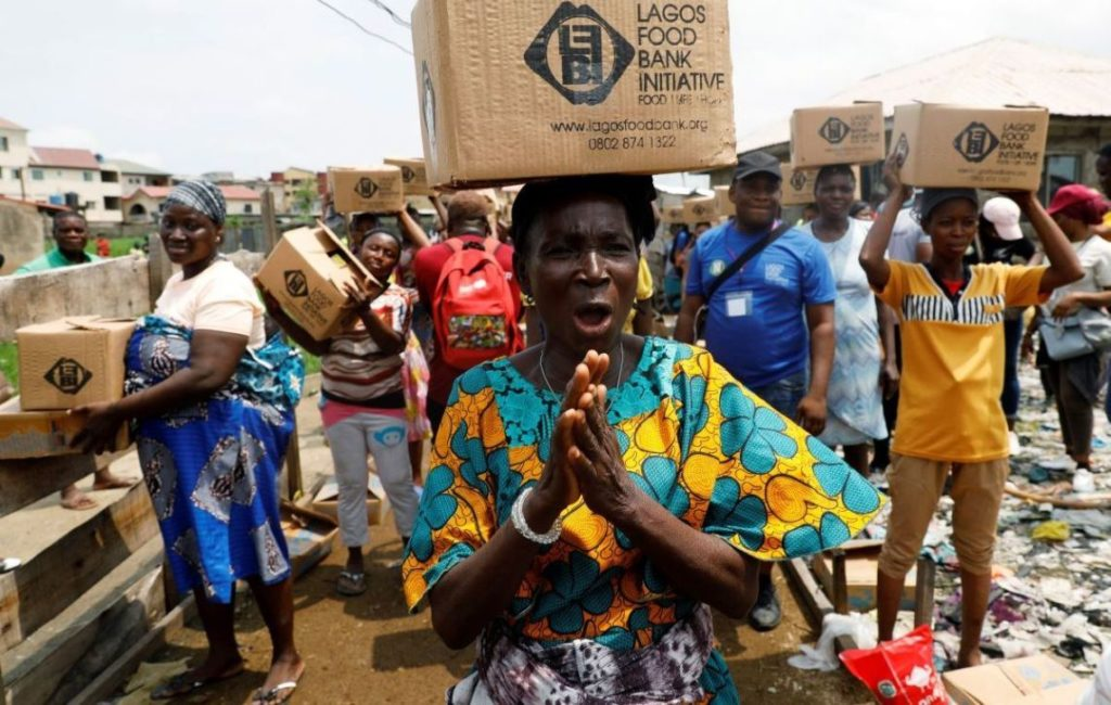 Women queue for food parcels during distribution by volunteers of the Lagos food bank initiative in a community in Oworoshoki, Lagos, Nigeria July 10, 2021. Picture taken July 10, 2021. REUTERS/Temilade Adelaja - RC2PHO9CCX6K