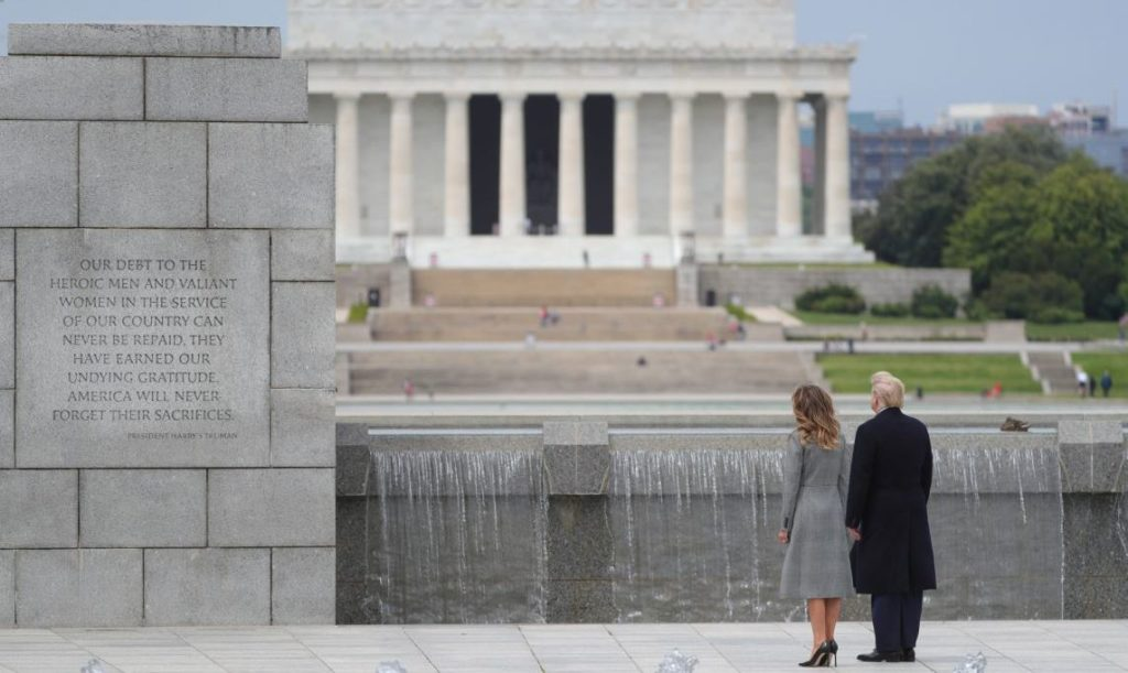 U.S. President Donald Trump and first lady Melania Trump look at an inscription on the World War II Memorial with the Lincoln Memorial in the background as they participate in a Victory in Europe Day 75th anniversary ceremony in Washington, U.S., May 8, 2020. REUTERS/Tom Brenner - RC2FKG9XNZA1