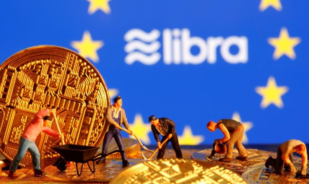 Small toy figures are seen on representations of the virtual currency before the displayed European Union flag and the Facebook Libra logo in this illustration picture, October 20, 2019. REUTERS/Dado Ruvic/Illustration - RC1D369C0990