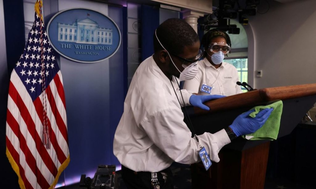 Workers disinfect the podium before the start of U.S. President Donald Trump's daily coronavirus disease (COVID-19) outbreak task force briefing at the White House in Washington, U.S. April 9, 2020.  REUTERS/Jonathan Ernst - RC281G9Z7ATO