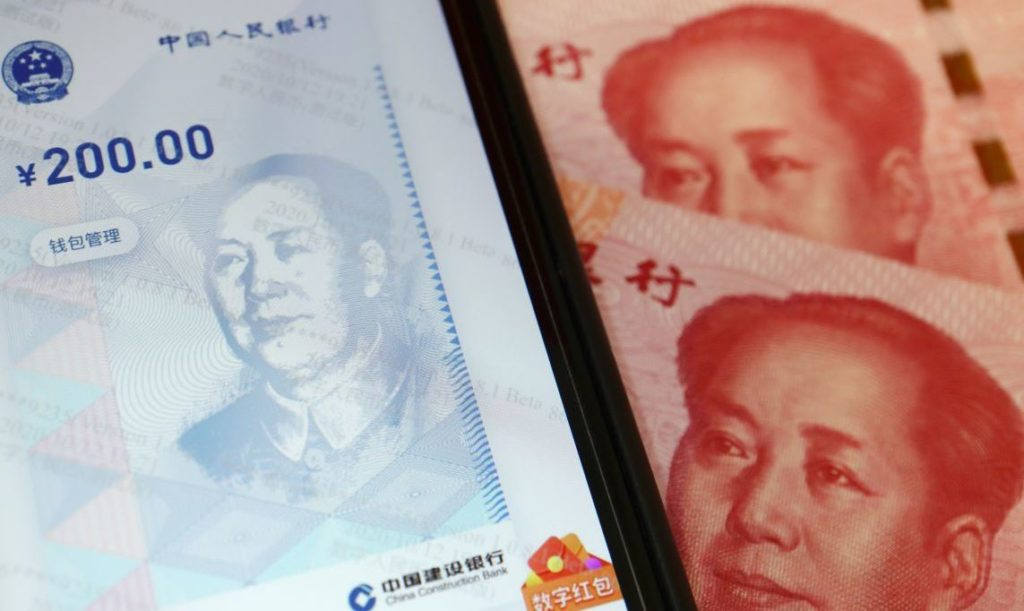 China's official app for digital yuan is seen on a mobile phone next to 100-yuan banknotes in this illustration picture taken October 16, 2020. REUTERS/Florence Lo/Illustration - RC2LLJ95Z3PQ