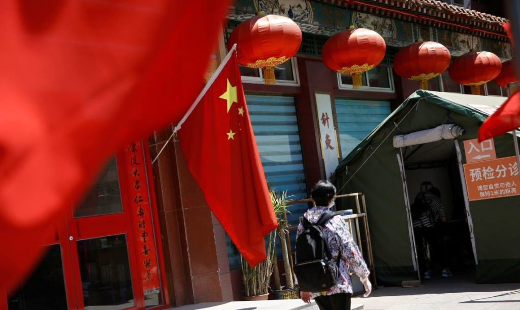 A woman walks outside a traditional Chinese medicine (TCM) hospital decorated with a Chinese flag following the coronavirus disease (COVID-19) outbreak, in Beijing, China May 19, 2020.  REUTERS/Tingshu Wang - RC2LRG9U93HO