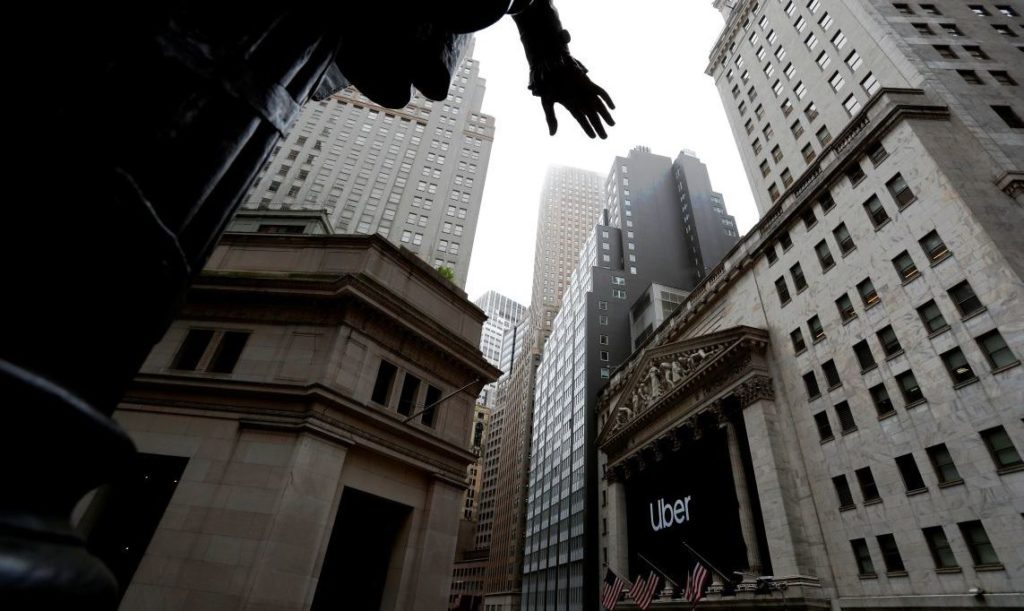 A banner announcing the IPO of Uber Technologies Inc. hangs outside the New York Stock Exchange (NYSE) as seen from beneath a statue of former U.S. President George Washington, at Federal Hall on Wall Street, in New York, U.S., May 10, 2019. REUTERS/Andrew Kelly - RC1CDFEFD080