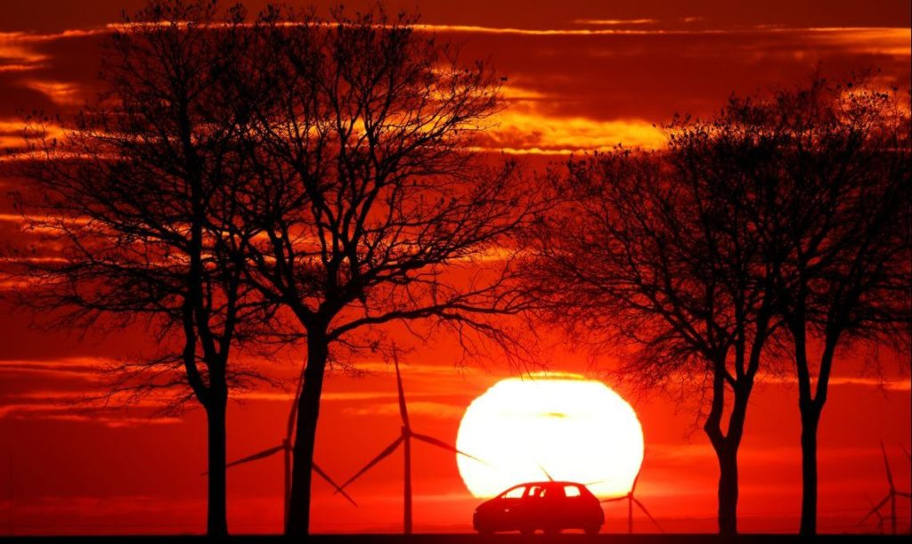 A car drives in front of power-generating windmill turbines on the Cambrai-Arras road during sunset in Bourlon, France, February 12, 2021. REUTERS/Pascal Rossignol - RC25RL99H50F