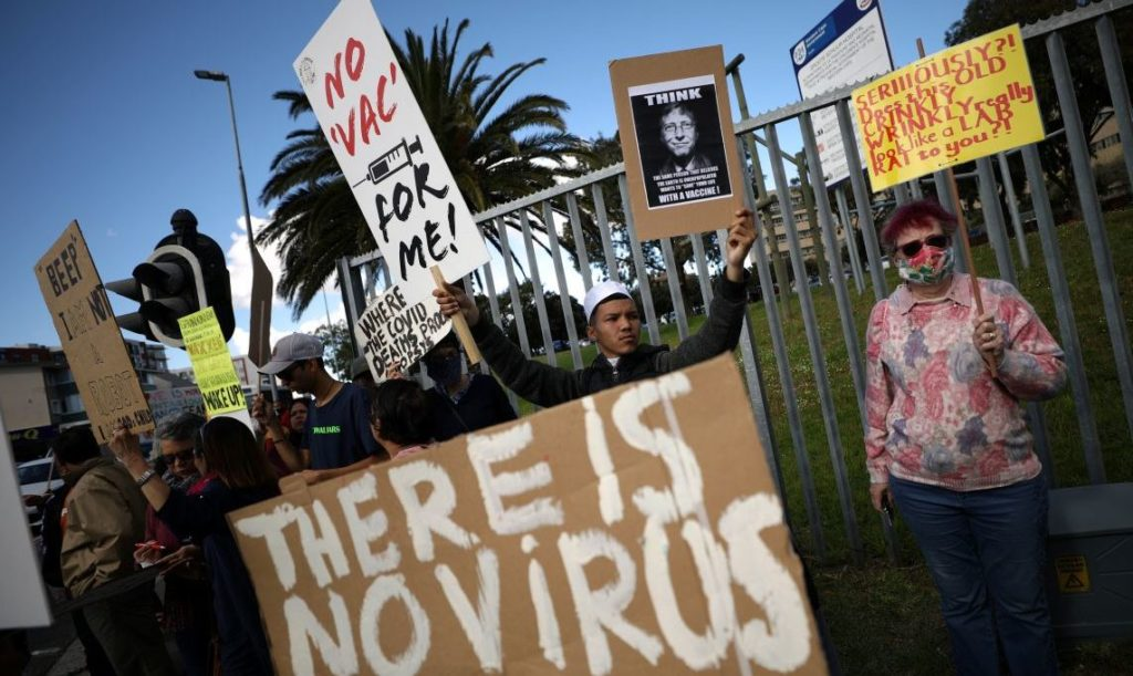 Anti-vaccine protestors hold placards a day after the country opened coronavirus disease (COVID-19) vaccinations for everyone 18 years old and above, outside Groote Schuur hospital in Cape Town, South Africa, August 21, 2021. REUTERS/Mike Hutchings - RC2M9P9TDC6Q